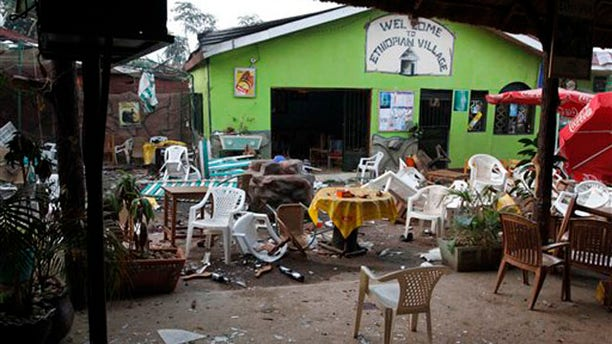 """Damaged chairs and tables are seen among the debris strewn outside the restaurant """"Ethiopian village"""" in Kampala, Uganda, July 12 after an explosion at the restaurant late Sunday. (AP Photo)"""