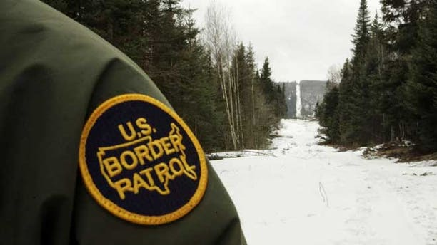 BEECHER FALLS, VT - MARCH 23:  A U.S. Border Patrol agent stands along the boundary marker cut into the forest marking the line between Canadian territory on the right and the United States March 23, 2006 near Beecher Falls, Vermont. As American politicians continue to debate immigration reform, Border Patrol agents work the northern border to prevent illegal entry.  (Photo by Joe Raedle/Getty Images)