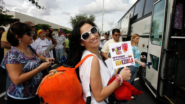Oct. 6th, 2012: Adrea Leon holds a sign saying she supports the elections in Venezuela as she boards one of fifty buses traveling to New Orleans from Miami to vote in the Venezuelan election.