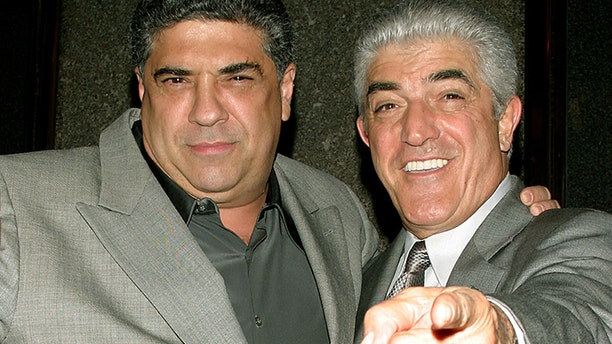 """Actors Vincent Pastore (L) and Frank Vincent point at the photographers as they arrive for the fifth season premiere of the HBO series """"The Sopranos,"""" in New York March 2, 2004. - PBEAHUOKKBB"""