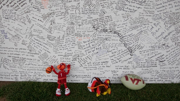 In this April 28, 2007 file photo, a memorial board sits under a tent with items that were placed in front of it, on the Drillfield on the Virginia Tech campus in Blacksburg, Va.
