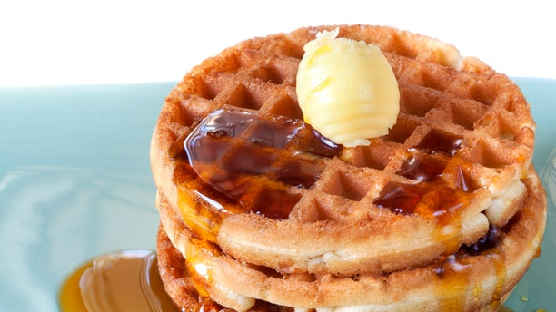 Stack of waffles with maple syrup and butter.