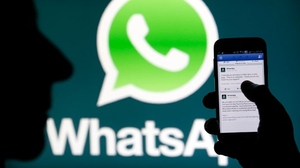 A Whatsapp App logo is seen behind a Samsung Galaxy S4 phone that is logged on to Facebook. Facebook Inc will buy fast-growing mobile-messaging startup WhatsApp for $19 billion in cash and stock in a landmark deal that places the world's largest social network closer to the heart of mobile communications and may bring younger users into the fold.