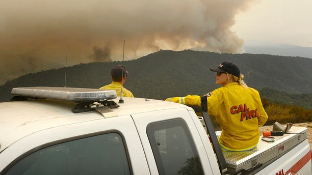 Aug. 1, 2016: Firefighters keep a lookout from Sky Ranch off Cachagua Grade as smoke and flames from a back burn light up a ridge to the south in east Carmel Valley, Calif.