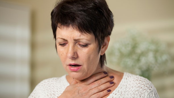 An unidentified woman suffers from a sore throat.