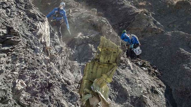 In this photo provided April 3, 2015 by the French Interior Ministry, French emergency rescue services work among debris of the Germanwings passenger jet at the crash site near Seyne-les-Alpes, France.