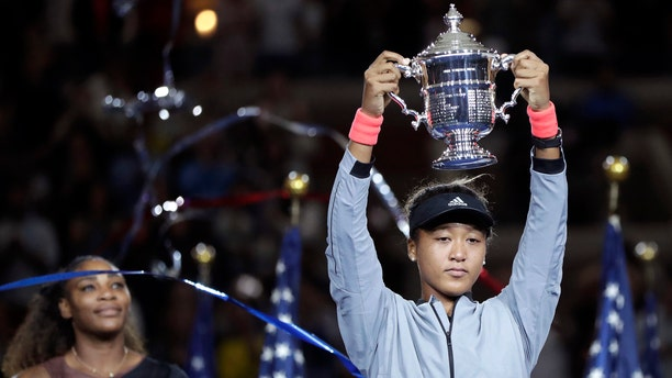 aomi Osaka, of Japan, holds the trophy after defeating Serena Williams in the women's final of the U.S. Open tennis tournament, Saturday, Sept. 8, 2018, in New York.