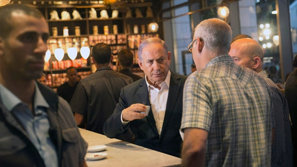 Israeli Prime Minister Benjamin Netanyahu sits at the scene of Wednesday's shooting attack at a Tel Aviv restaurant, Thursday, June 9, 2016. Israel on Thursday imposed travel restrictions on tens of thousands of Palestinians and sent hundreds of additional troops into the West Bank in response to a deadly shooting at a popular Tel Aviv tourist spot, but as the nation's leaders vowed tough responses, they stopped short of taking wider scale military action. (AP Photo/Tomer Appelbaum)   ISRAEL OUT