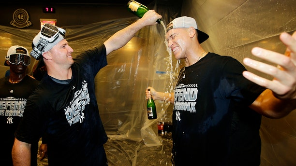 New York Yankees' Aaron Judge, right, celebrates with teammates after they clinched wildcard playoff berth with an 3-2 win over the Baltimore Orioles in New York, Sept. 22, 2018