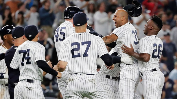 New York Yankees' Aaron Hicks (31) celebrates with teammates after hitting an RBI double during the 11th inning against the Baltimore Orioles in New York, Sept. 22, 2018. The Yankees won 3-2.