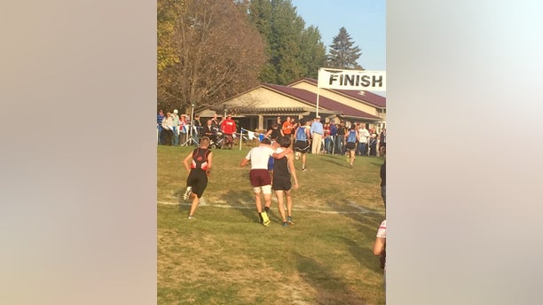 Seen from behind, Zach Hougland (left) helps Garret Hinson (right) walk toward the finish line.
