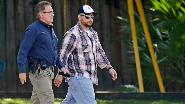 Sept. 9, 2013: George Zimmerman, right, is escorted to a home by a Lake Mary police officer in Lake Mary, Fla., after a domestic incident in the neighborhood where Zimmerman and his wife Shellie had lived during his murder trial. Zimmerman's wife says on a 911 call that her estranged husband punched her father in the nose, grabbed an iPad out of her hand and smashed it and threatened them both with a gun. Zimmerman was recently found not guilty for the 2012 shooting death of Trayvon Martin. (AP/John Raoux)