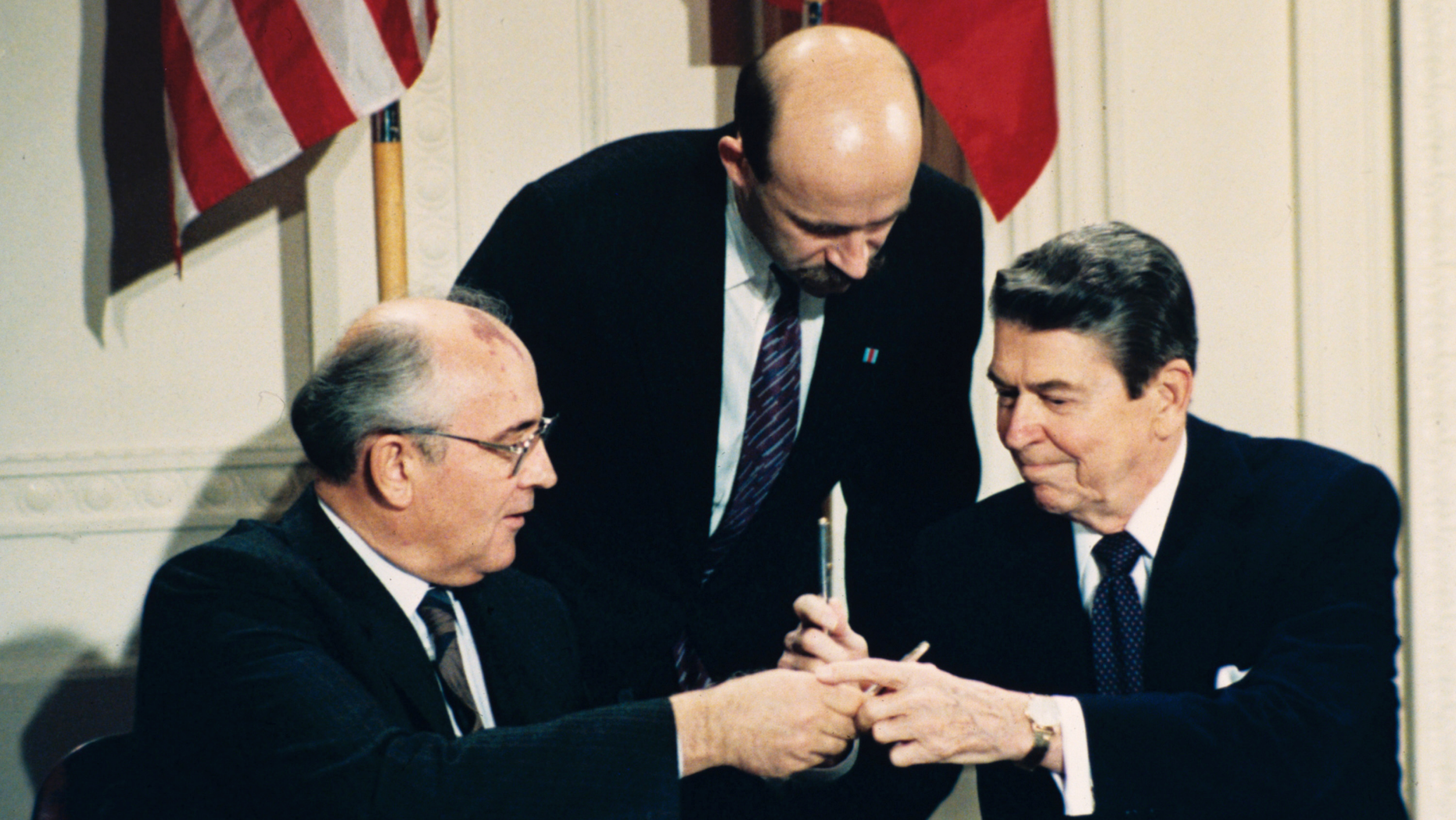 FILE - In this Dec. 8, 1987 file photo U.S. President Ronald Reagan, right, and Soviet leader Mikhail Gorbachev exchange pens during the Intermediate Range Nuclear Forces Treaty signing ceremony in the White House East Room in Washington, D.C. Gorbachev's translator Pavel Palazhchenko stands in the middle. Trump's announcement that the United States would leave the Intermediate-Range Nuclear Forces, or INF, treaty brought sharp criticism on Sunday Oct. 21, 2018, from Russian officials and from former Soviet President Mikhail Gorbachev, who signed the treaty in 1987 with President Ronald Reagan. (AP Photo/Bob Daugherty, File)