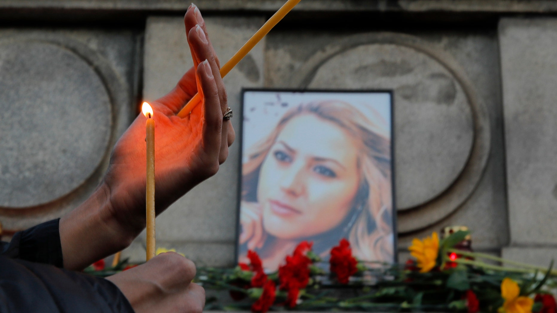 Oct. 8: A woman holds a candle next to a portrait of slain television reporter Viktoria Marinova during a vigil at the Liberty Monument in Ruse, Bulgaria.