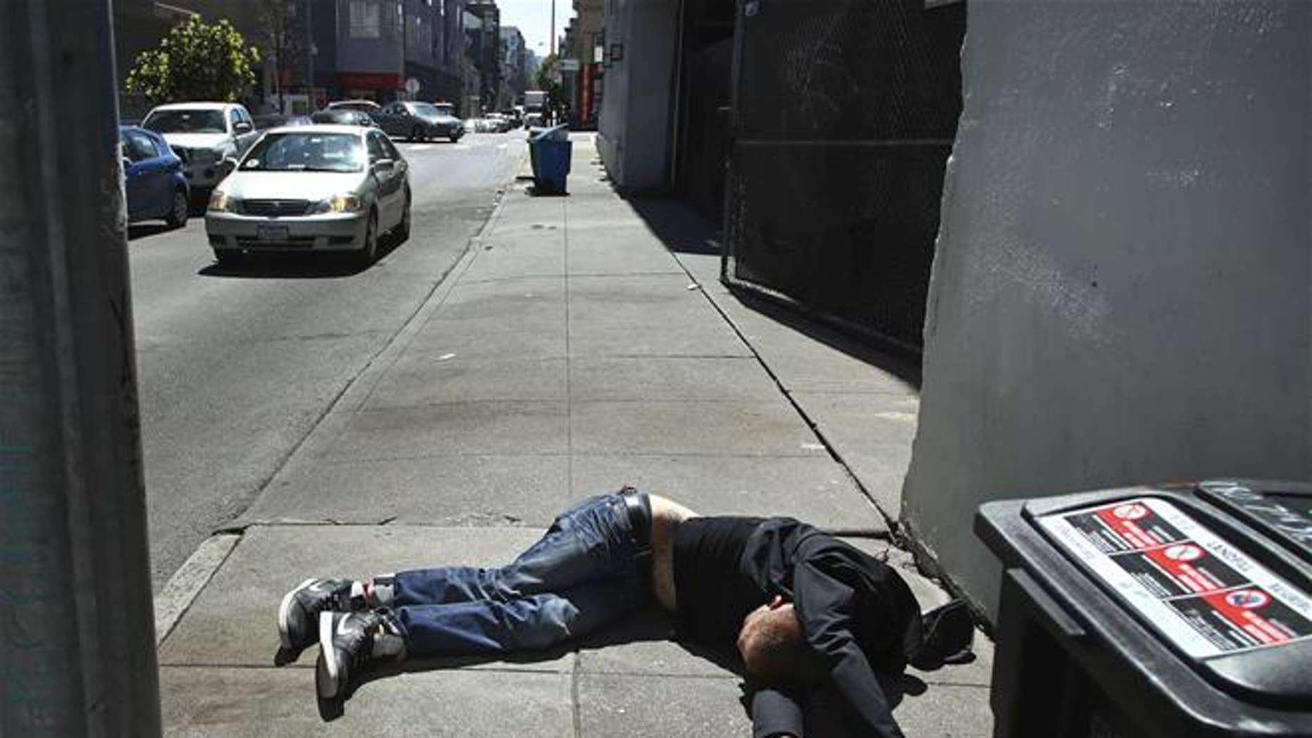 In this April 26, 2018, file photo, a man lies on the sidewalk beside a recyclable trash bin in San Francisco.