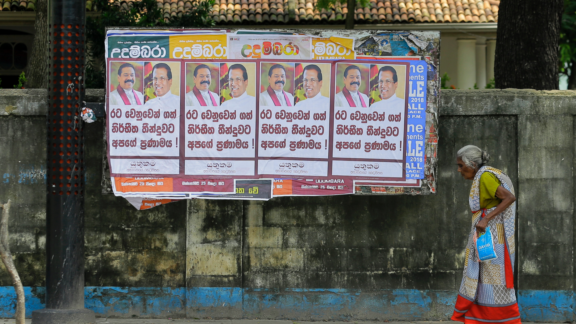 """A Sri Lankan woman walks past a notice board covered with posters carrying portraits of President Maithripala Sirisena and newly appointed Prime Minster Mahinda Rajapaksa at a street in Colombo, Sri Lanka, Sunday, Oct. 28, 2018. Sri Lanka's president suspended Parliament even as the prime minister he fired the previous day claimed he has majority support, adding to a growing political crisis in the South Asian island nation. Posters read """" Our respect for the decision took on behalf of the country."""" (AP Photo/Eranga Jayawardena)"""
