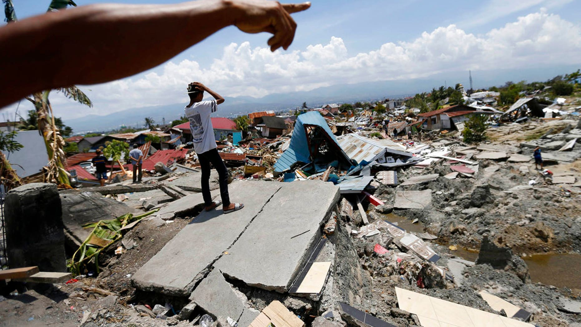 FILE: Indonesian men survey the damage in Balaroa neighborhood in Palu, Central Sulawesi, Indonesia.