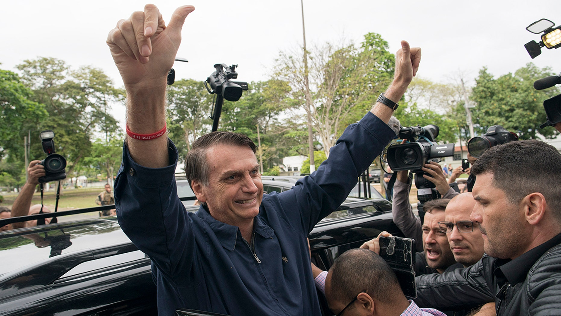 Presidential frontrunner Jair Bolsonaro, of the Social Liberal Party, flashes thumbs up to supporters after voting at a polling station in Rio de Janeiro, Brazil, Sunday, Oct. 7, 2018. (AP Photo/Leo Correa)