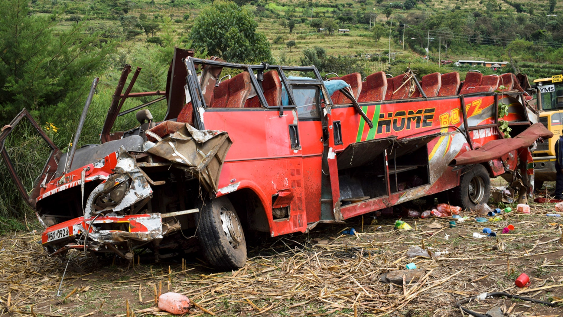 The wrecked bus is seen at the scene of a bus crash near Kericho in western Kenya Wednesday, Oct. 10, 2018. An official says at least 50 people have died after the bus they were traveling in left the road, rolled down a slope and crashed near the western Kenyan town of Kericho.