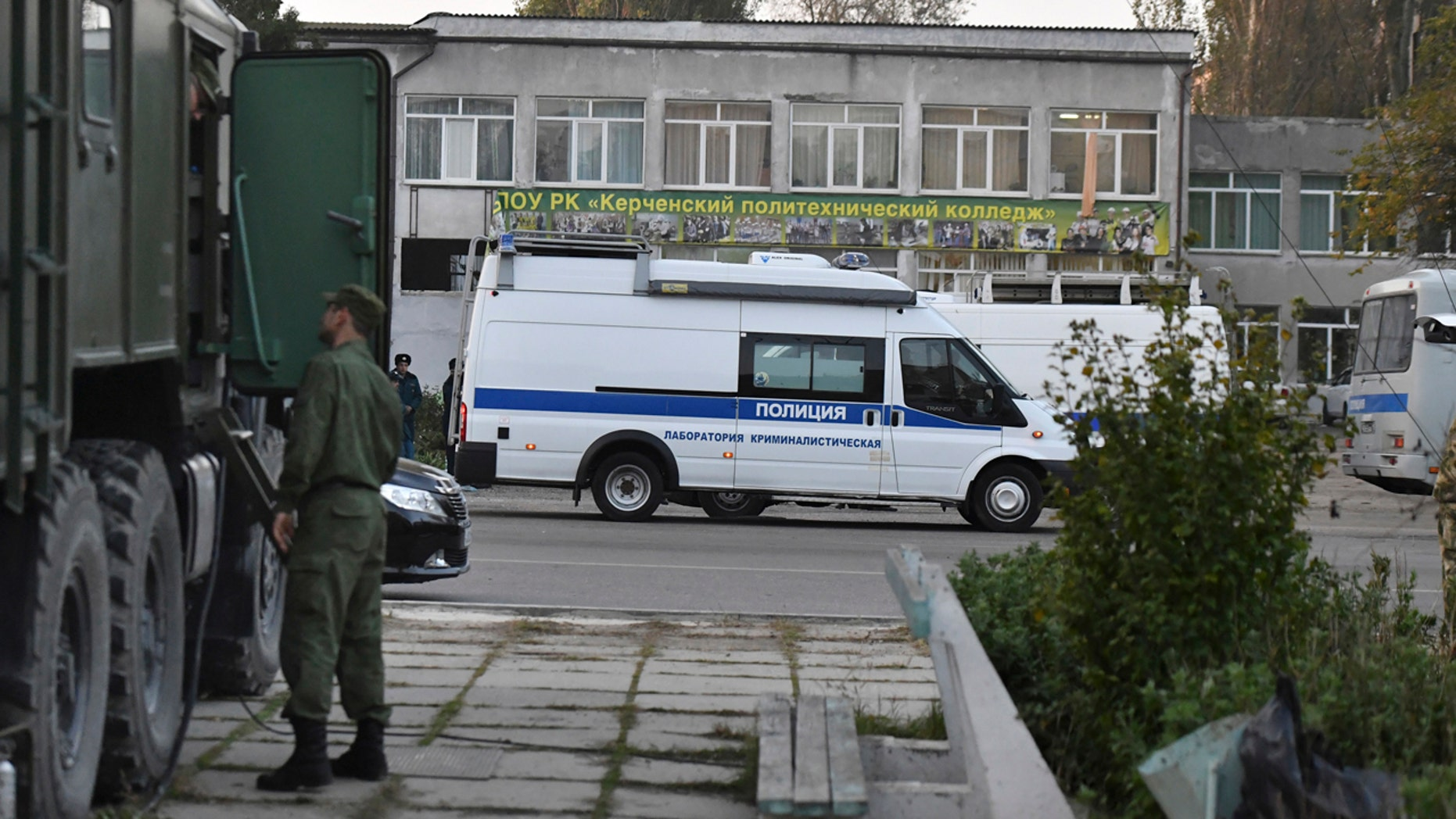 Police vehicles are parked near a vocational college in Kerch, Crimea, Thursday, Oct. 18, 2018.