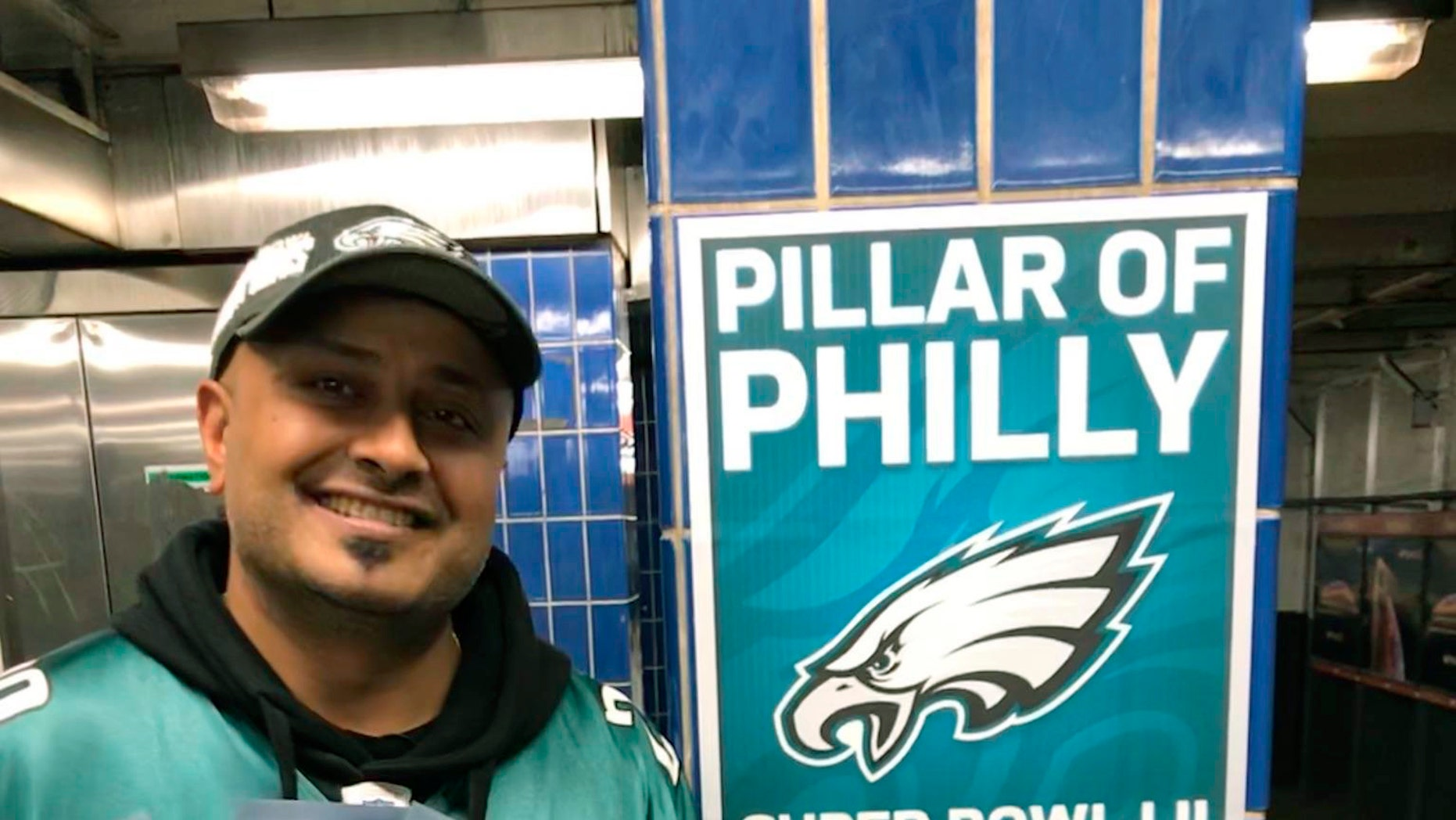 In this October 2018 photo, Philadelphia Eagles fan Jigar Desai poses with tickets to an Oct. 28 football game between the Eagles and the Jacksonville Jaguars in front of the subway pillar he ran into earlier this year at Ellsworth Station on the Broad Street subway line in Philadelphia.