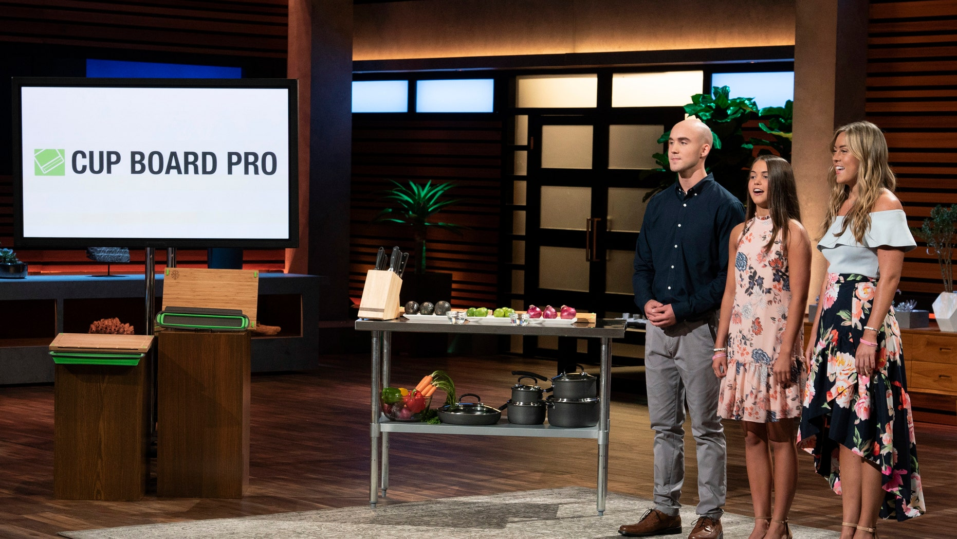 """In this image provided by ABC, Kevin Young's children present the product of their late father, Cup Board Pro, which is a chopping block that features a detachable bowl for clean up, on a """"Shark Tank"""" episode that aired on Sunday, Oct. 21, 2018."""