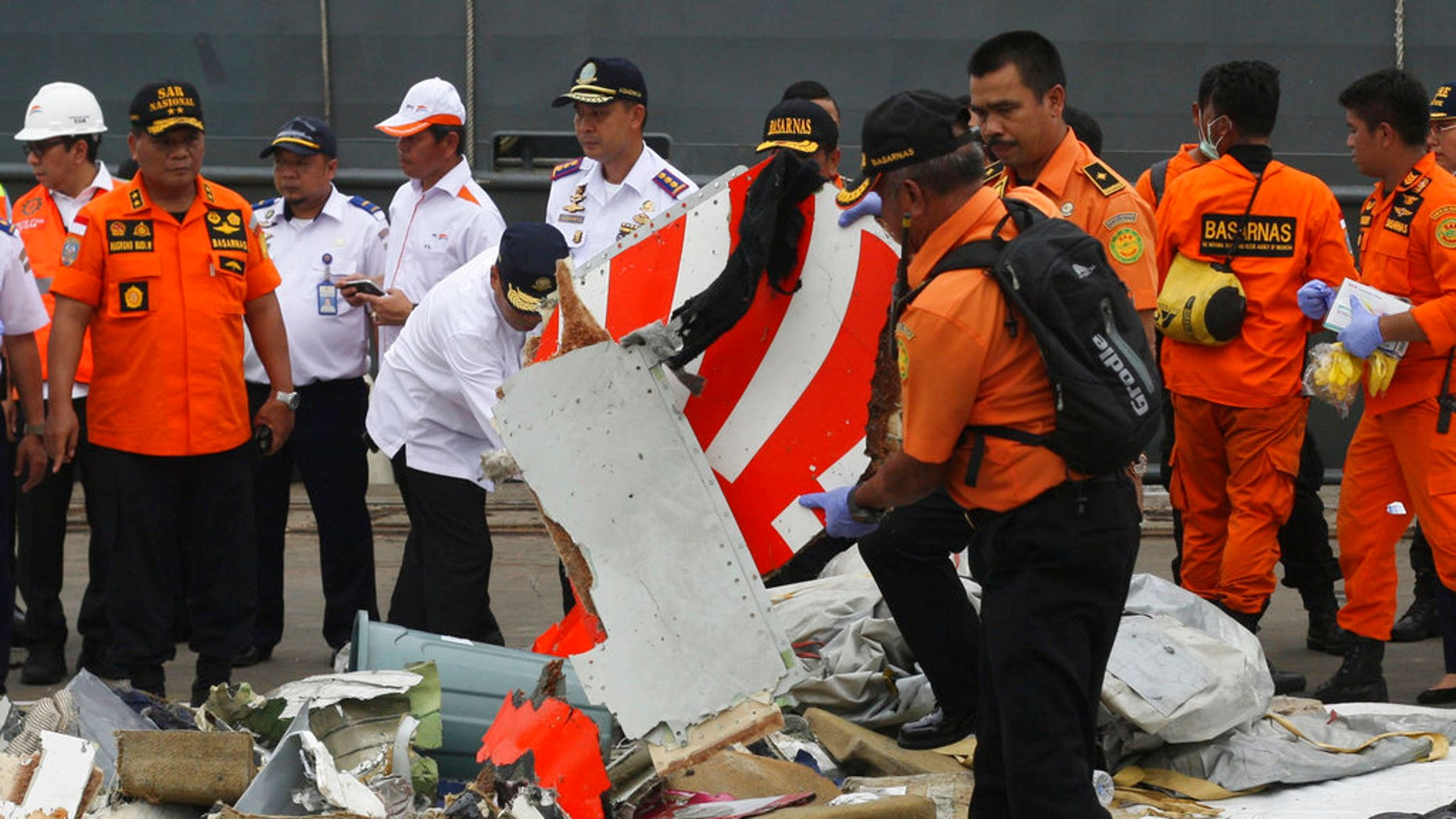 FILE: A rescuer inspects a part of Lion Air plane flight JT 610 retrieved from the waters where it's believed to have crashed at Tanjung Priok Port in Jakarta, Indonesia, Tuesday.