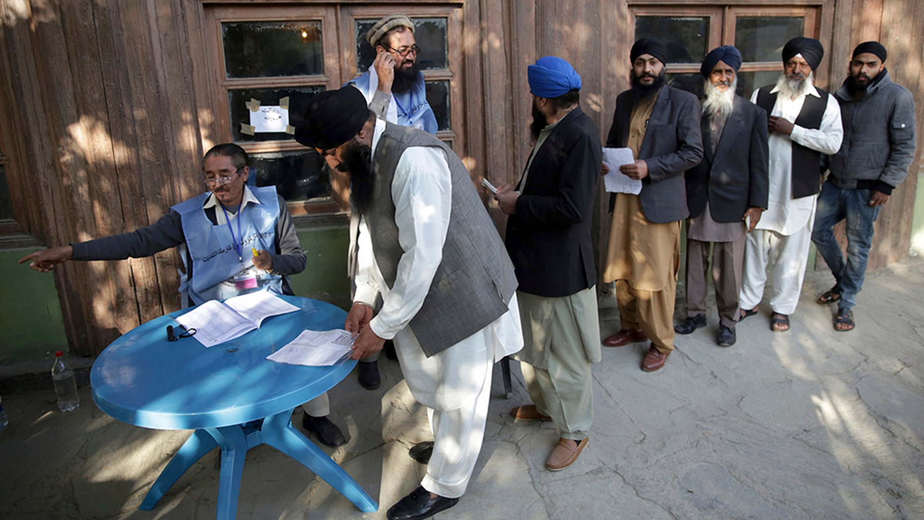 Voters from the minority Sikh register to cast ballots in parliamentary elections in  Kabul, Afghanistan, Saturday. Tens of thousands of Afghan forces fanned out across the country as voting began in the elections that followed a campaign marred by relentless violence. (AP Photo/Massoud Hossaini)