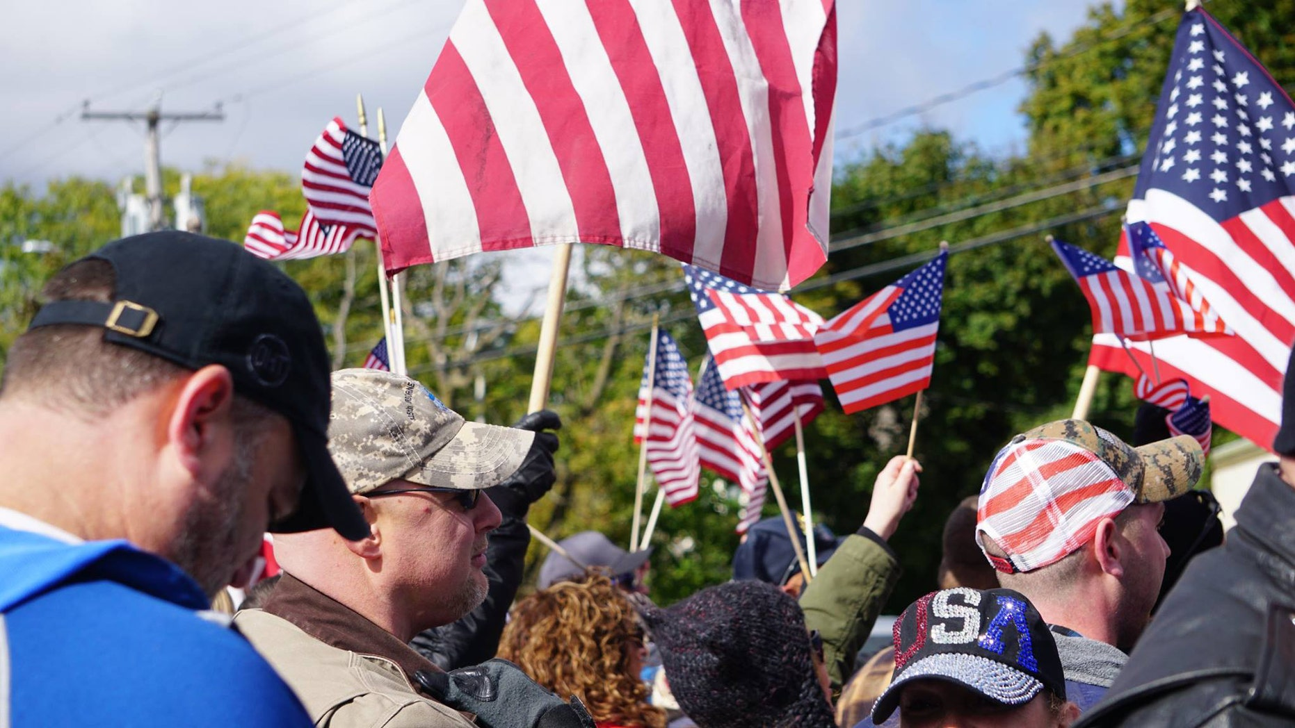 "Supporters wave flags at the ""American flag appreciation walk"" in New Paltz, New York Sunday afternoon."