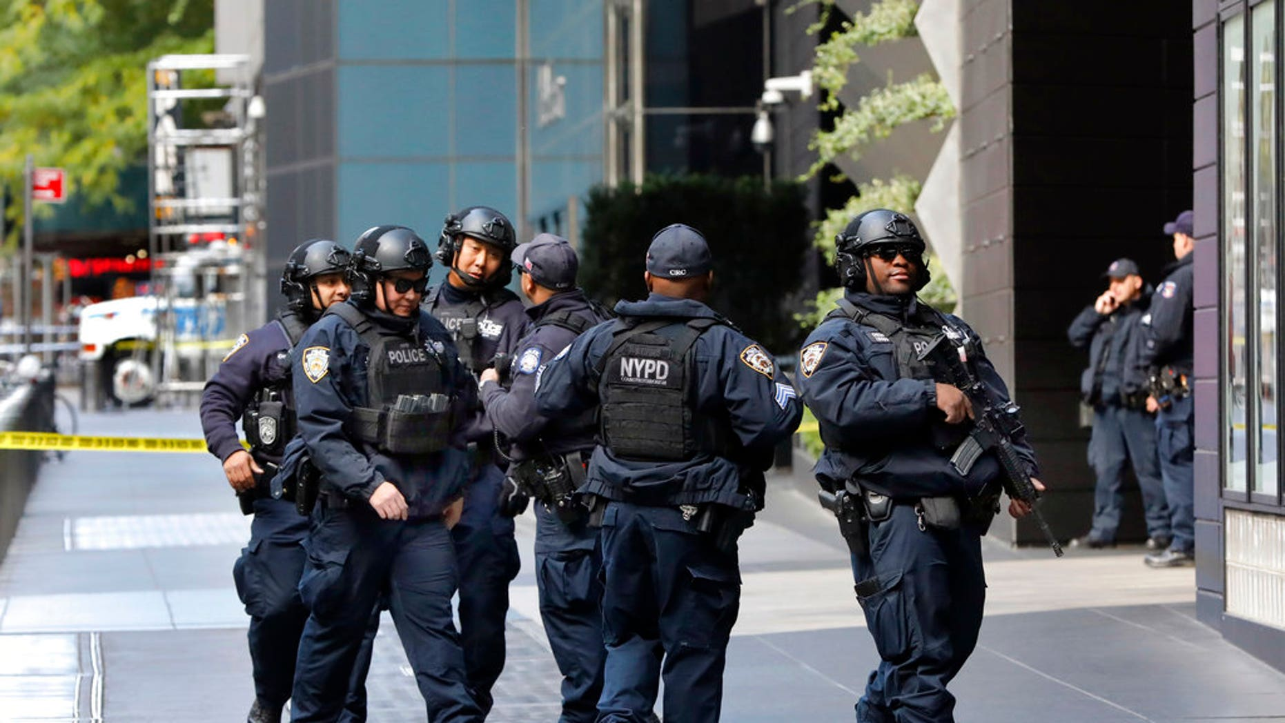 New York City Police Dept. officers gather outside the Time Warner Center, in New York, Wednesday, Oct. 24, 2018. A police bomb squad was sent to CNN's offices in New York City and the newsroom was evacuated because of a suspicious package. (AP Photo/Richard Drew)