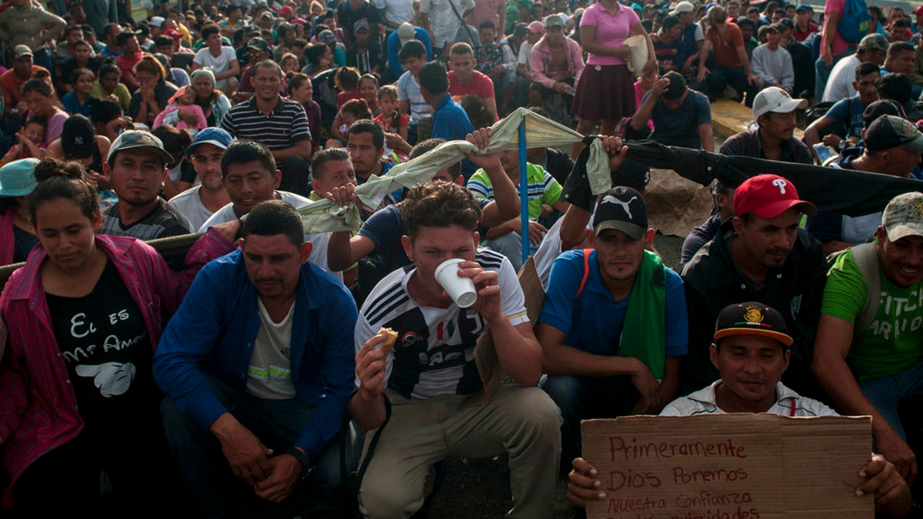 Honduras migrants wait to be attended by Mexican migration authorities on a bridge that stretches over the Suchiate River, connecting Guatemala and Mexico, in Tecun Uman, Guatemala. (AP Photo/Oliver de Ros)