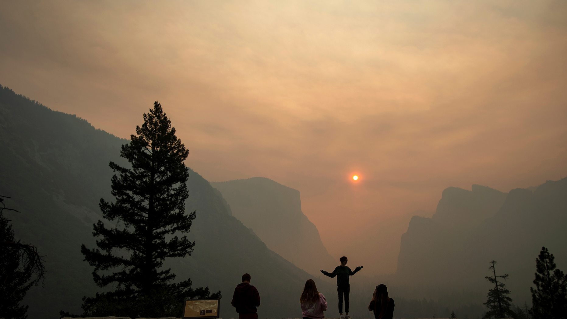 FILE - In this July 25, 2018 file photo, Hannah Whyatt poses for a friend's photo as smoke from the Ferguson fire fills Yosemite Valley in Yosemite National Park, Calif. Authorities say the Ferguson fire, that killed two firefighters and destroyed nearly a dozen buildings in Northern California, was caused by a vehicle. The U.S. Forest Service on Friday, Oct. 5, 2018, said investigators determined that a hot catalytic converter ignited dry roadside vegetation. However, investigators haven't identified the vehicle. (AP Photo/Noah Berger, File)