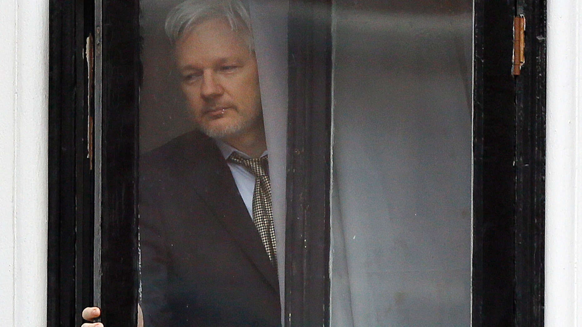 FILE - In this Feb. 5, 2016 file photo, Wikileaks founder Julian Assange walks onto the balcony of the Ecuadorean Embassy in London. An Ecuadorean judge ruled Monday, Oct. 29, 2018 against a request by him to loosen requirements he says are meant to push him out of the London embassy where he lives. (AP Photo/Kirsty Wigglesworth, File)