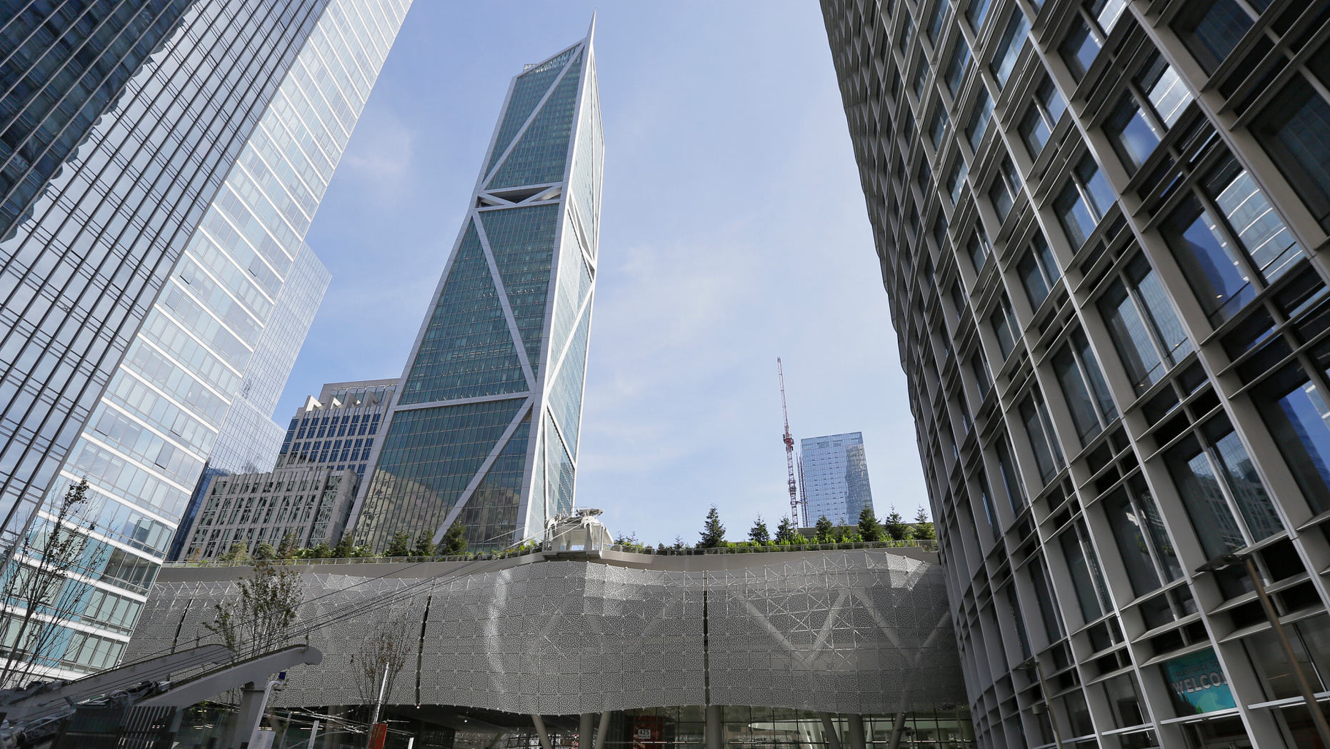 FILE--In this Sept. 27, 2018, file photo, people walk through main plaza entryway to the closed Salesforce Transit Center in San Francisco. As two of the city's most vaunted buildings sink or crack, an earthquake study released Thursday, Oct. 4,  recommended re-inspecting dozens of high-rises and beefing up construction codes for the growing crop of skyscrapers in the booming city. (AP Photo/Eric Risberg, file)
