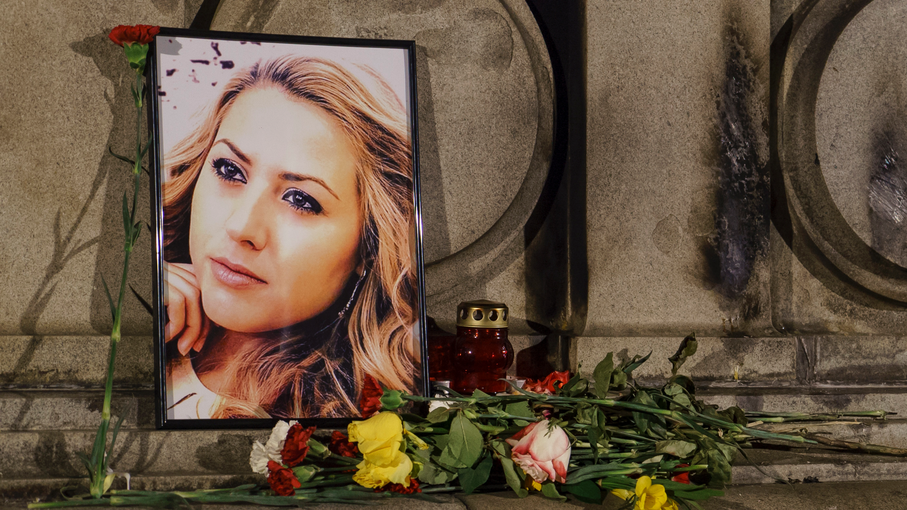 A portrait of slain television reporter Viktoria Marinova is placed on the Liberty Monument next to flowers and candles during a vigil in Ruse, Bulgaria, Tuesday, Oct. 9, 2018. Bulgarian police are investigating the rape, beating and slaying of Marinova, whose body was dumped near the Danube River after she reported on the possible misuse of European Union funds in Bulgaria. Authorities discovered the body of 30-year-old Viktoria Marinova on Saturday in the northern town of Ruse near the Romanian border. One Bulgarian media site demanded an EU investigation, fearing that Bulgarian officials were complicit in the corruption. (AP Photo/Filip Dvorski)