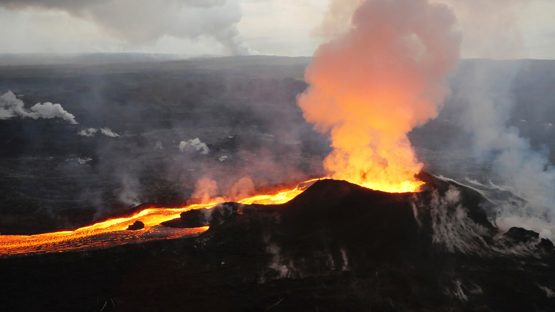 """FILE - In this Saturday, July 14, 2018 photo provided by the U.S. Geological Survey, lava from Kilauea volcano erupts in the Leilani Estates neighborhood near Pahoa, Hawaii. On Thursday, Oct. 25, 2018, government scientists updated 18 U.S. volcanoes as a """"very high threat"""" because of what's been happening inside them and how close they are to people. (U.S. Geological Survey via AP)"""