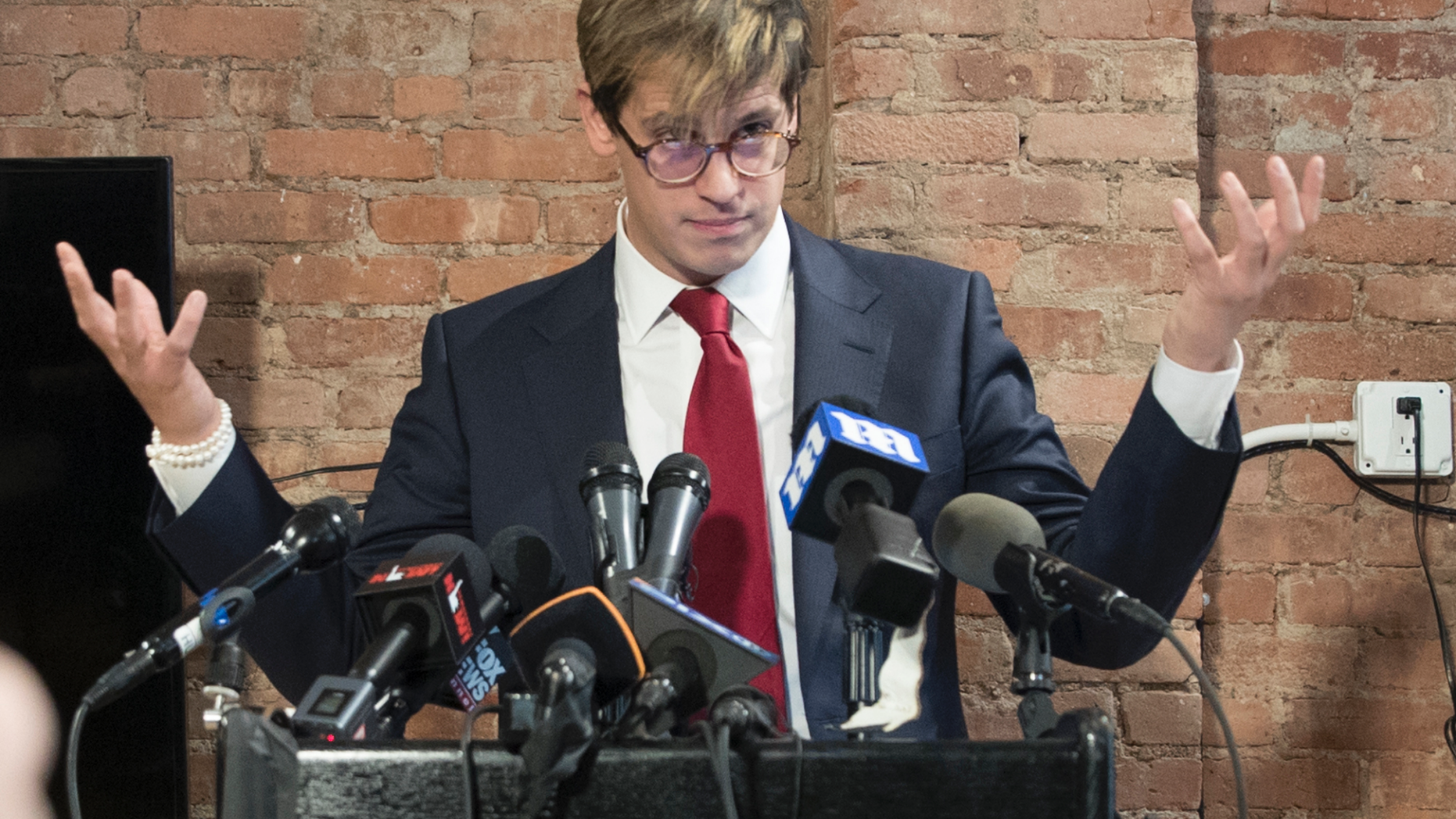 FILE- In this Feb. 21, 2017 file photo, Milo Yiannopoulos speaks during a news conference in New York. Citing safety concerns, New York University has postponed a speech by the right-wing provocateur that was scheduled for Halloween night, Wednesday, Oct. 31, 2018. (AP Photo/Mary Altaffer, File)