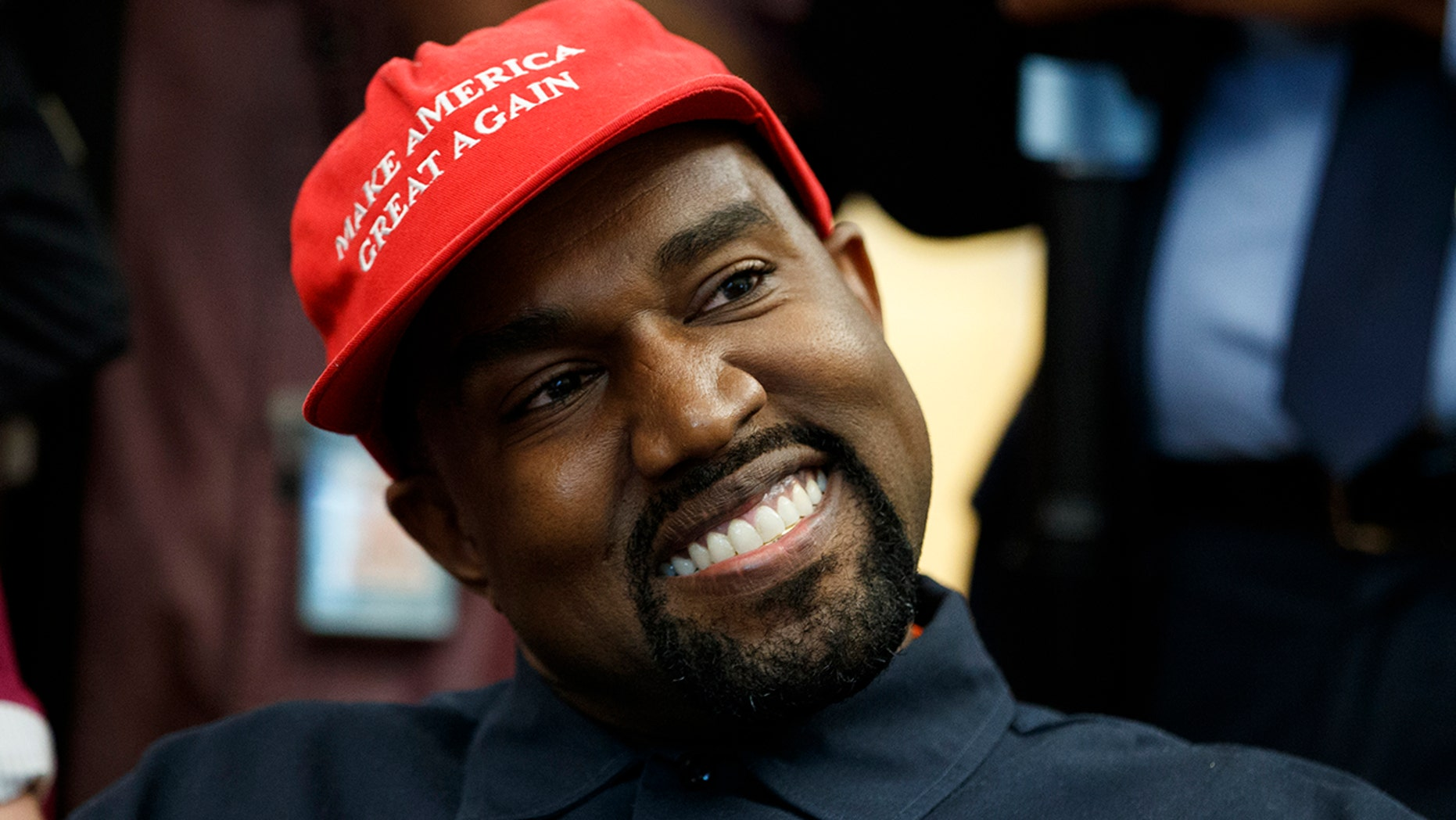 Rapper Kanye West smiles as he listens to a question from a reporter during a meeting in the Oval Office of the White House with President Donald Trump.