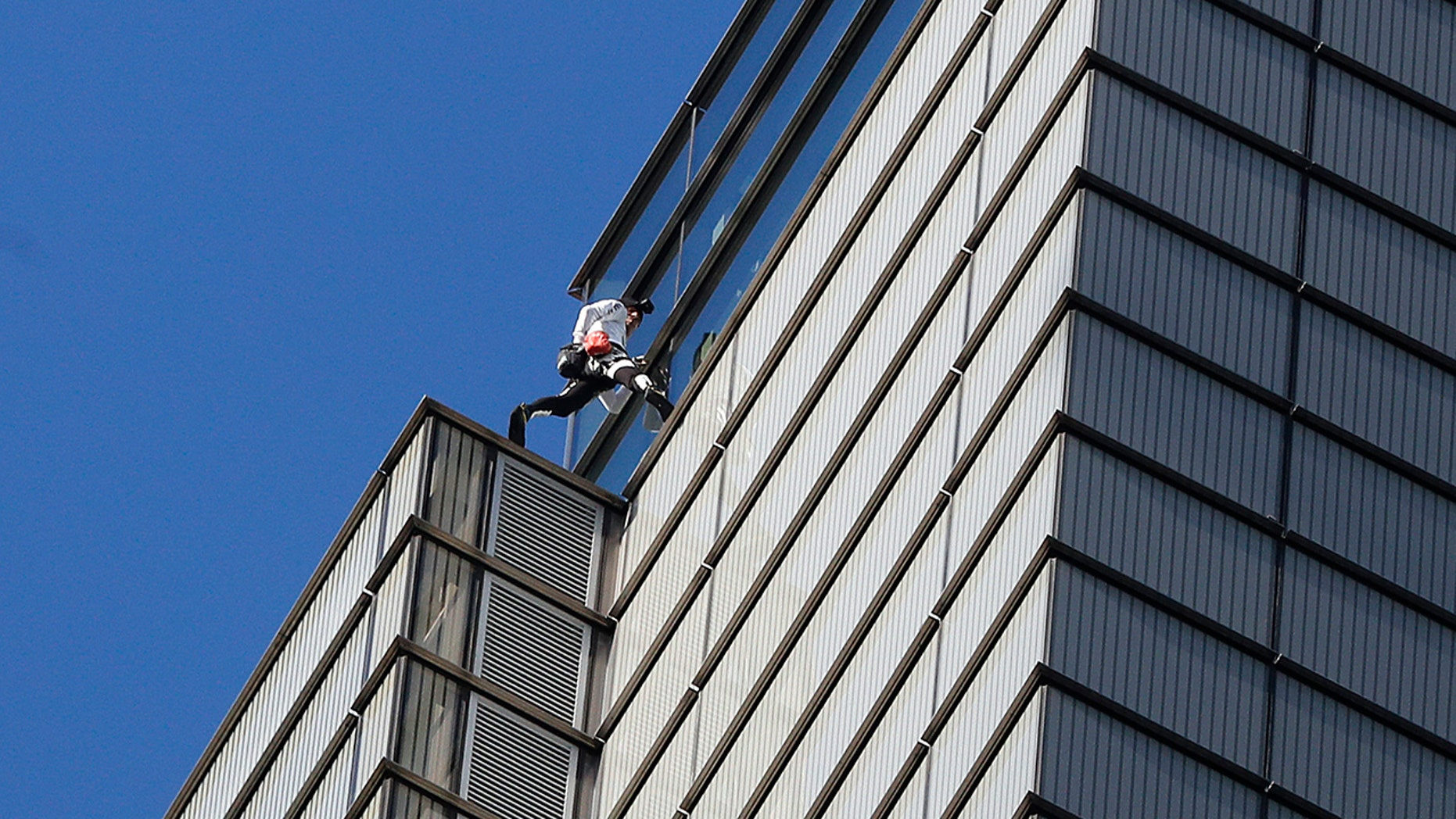 """Alain Robert, an urban climber dubbed the """"French Spider-Man,"""" completes his climb of the outside of Heron Tower building in the City of London, Thursday, Oct. 25, 2018."""