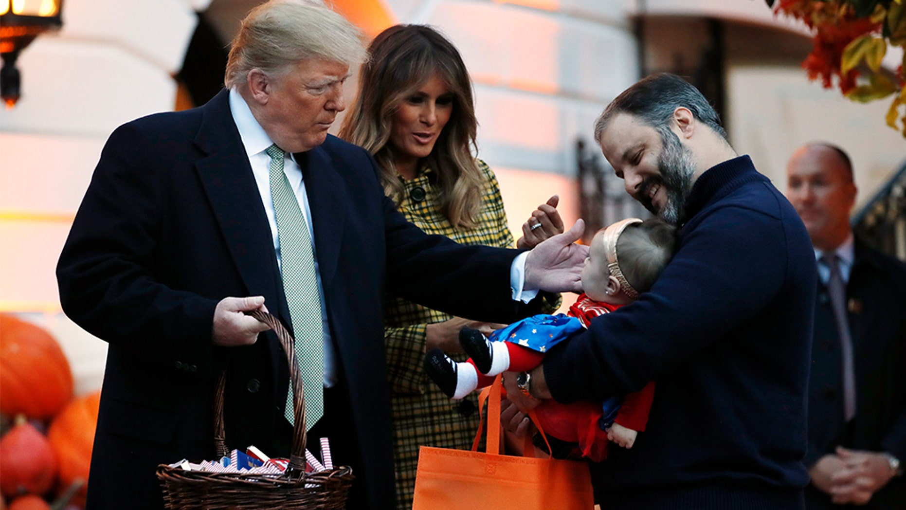 President Donald Trump and first lady Melania Trump greeting a baby in a superhero costume as they hand out candy to children during a Halloween trick-or-treat event at the White House.