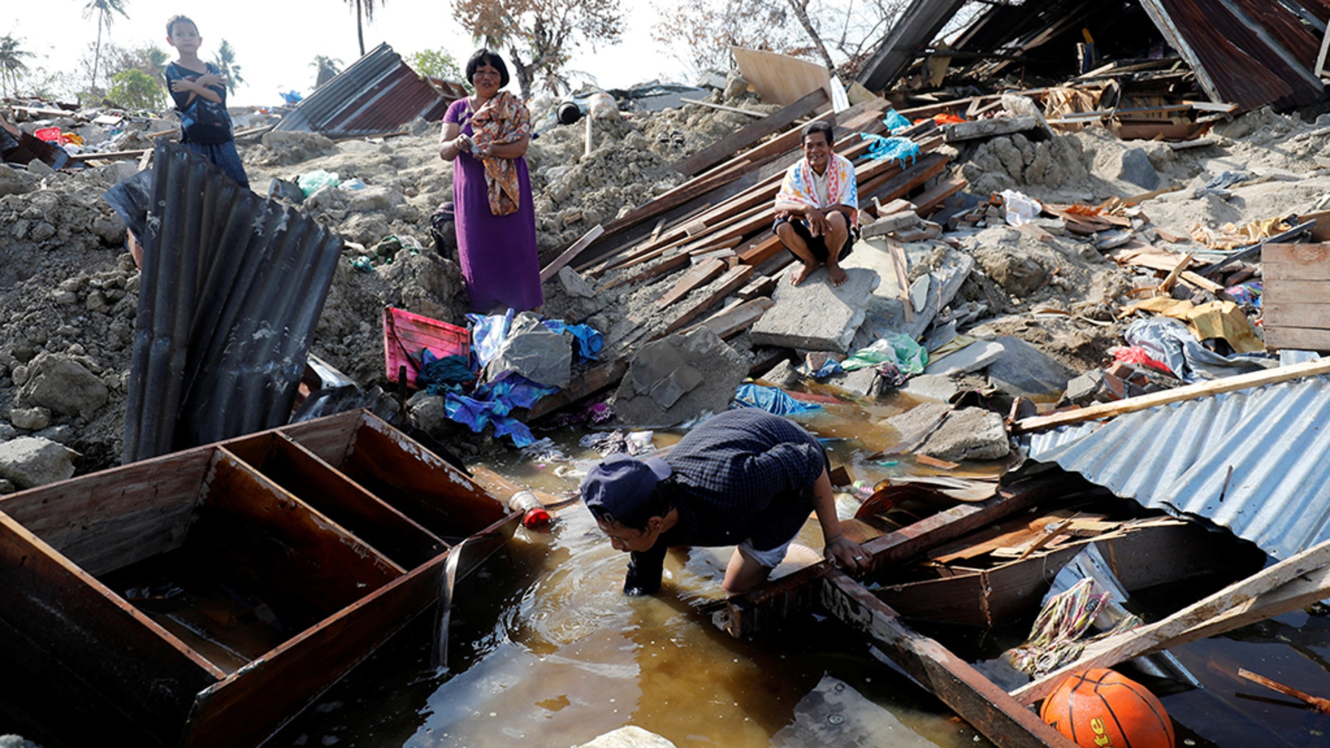 A family searches for their belongings in the remains of their home in the Petobo neighborhood, which was hit by an earthquake, in Palu, Central Sulawesi, Indonesia, Oct. 10, 2018.