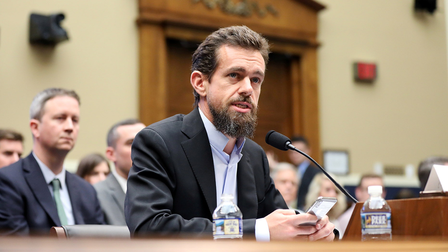Twitter co-founder Jack Dorsey holding a phone during a Sept. 5 appearance on Capitol Hill.