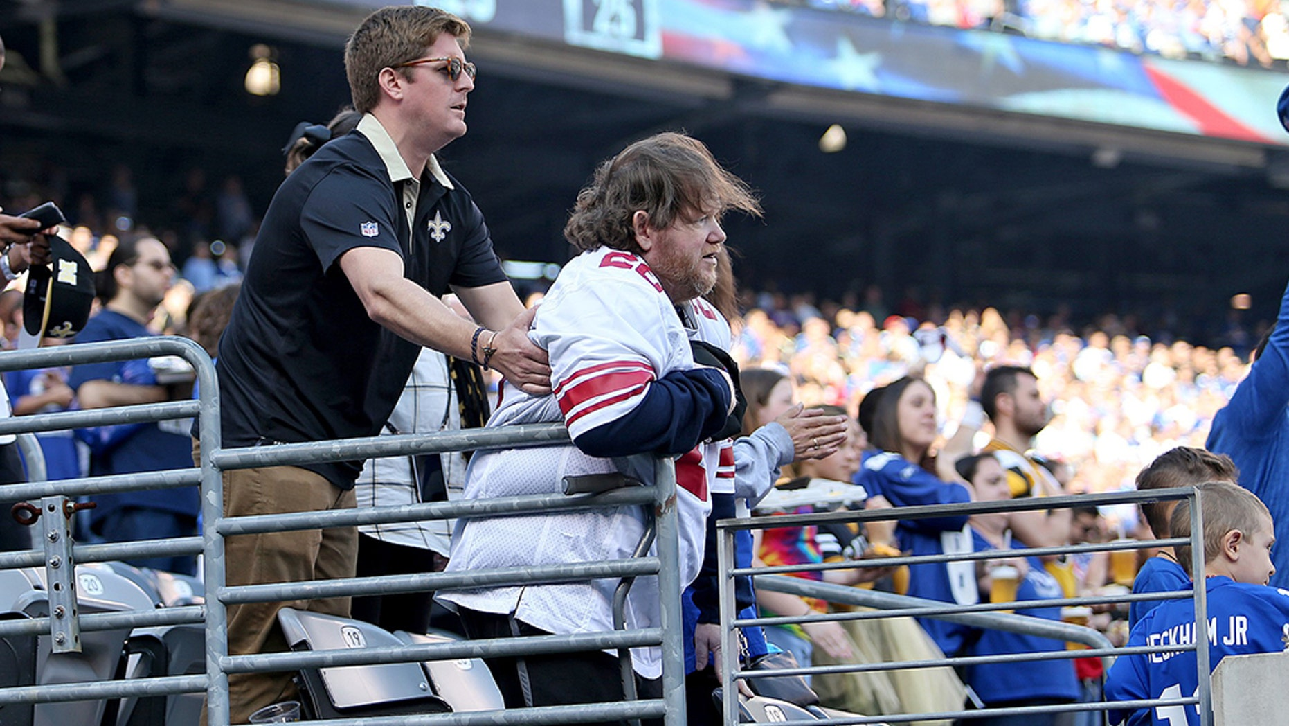 A Saints fans helps a disabled Giants fan sitting in front of him to stay standing during the National Anthem before the game on Sunday, September 30, 2018.