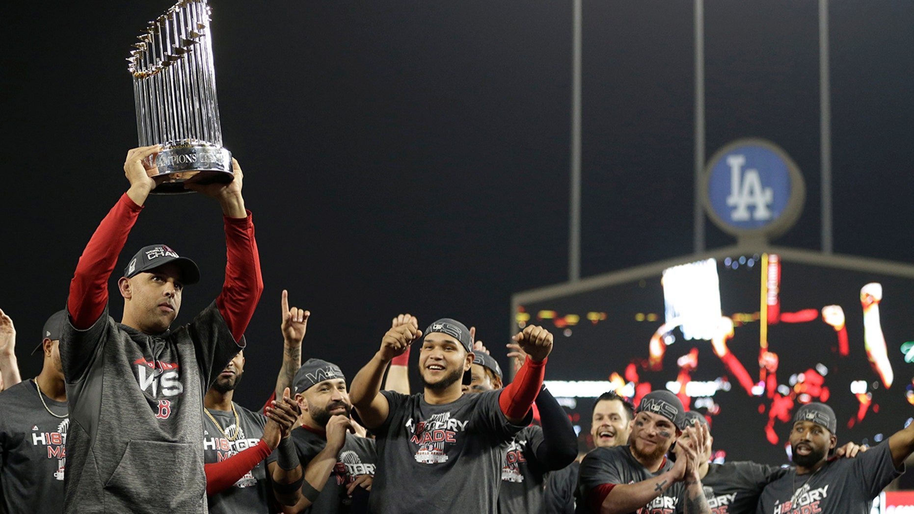 Boston Red Sox manager Alex Cora holds the championship trophy after Game 5 of baseball's World Series against the Los Angeles Dodgers on Sunday, Oct. 28, 2018, in Los Angeles..