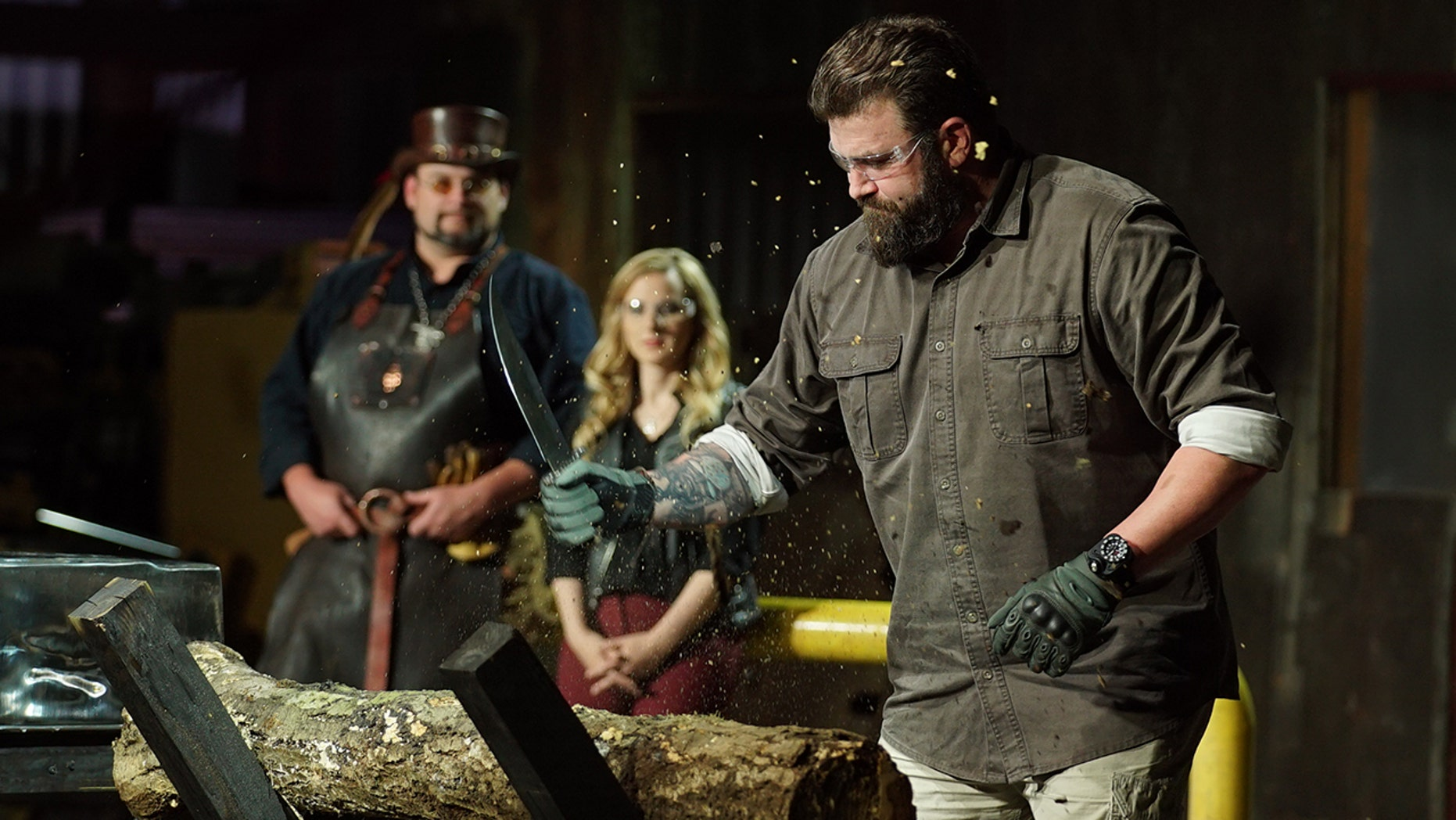 'Master of Arms' judge Zeke chopping at alog with contestants knife. Trent and Ashley in the background.