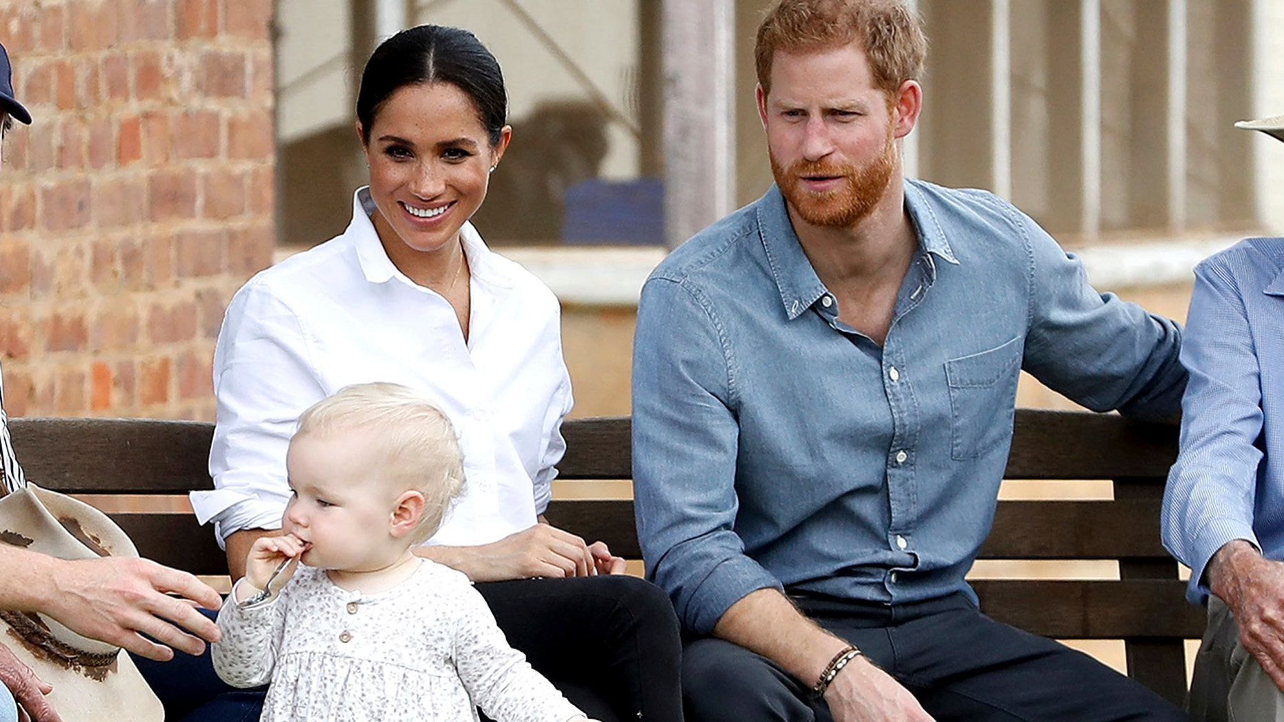 Britain's Prince Harry and Meghan, Duchess of Sussex sit down with the Woodleys family during a farm visit in Dubbo, Australia, Wednesday, Oct. 17, 2018. Prince Harry and his wife Meghan are on day two of their 16-day tour of Australia and the South Pacific. (Chris Jackson/Pool via AP)