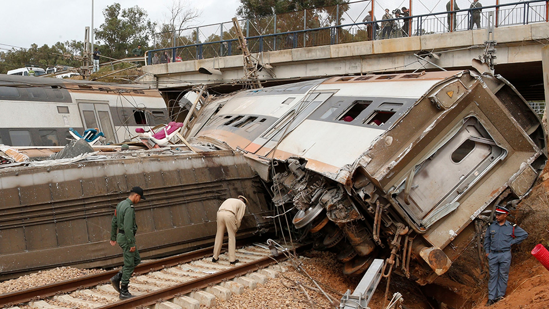 A police officer and train workers standing by a derailed train Tuesday near Sidi Bouknadel, Morocco.