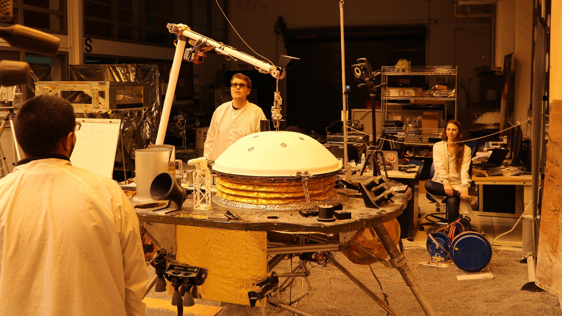 """NASA's InSight mission tests an engineering version of the spacecraft's robotic arm in a Mars-like environment at NASA's Jet Propulsion Laboratory. The five-fingered grapple on the end of the robotic arm is lifting up the Wind and Thermal Shield, a protective covering for InSight's seismometer. The test is being conducted under reddish """"Mars lighting"""" to simulate activities on the Red Planet. (Credit: NASA/JPL-Caltech)"""