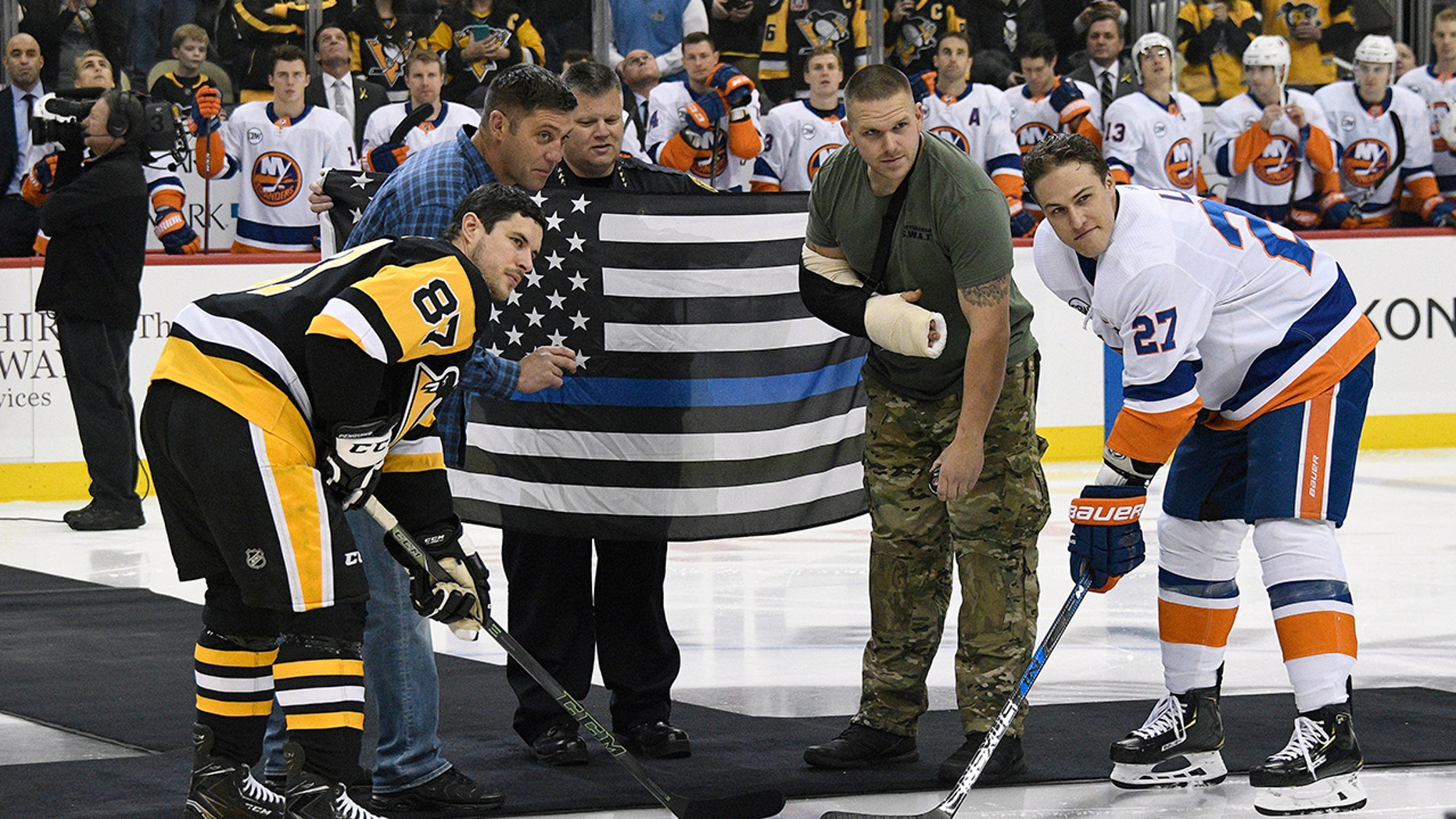 Pittsburgh Police Officer Mike Smidga, Pittsburgh Police Chief Scott Schubert and Officer Anthony Burke take part in a ceremonial puck drop with Pittsburgh Penguins center Sidney Crosby (87) and New York Islanders left wing Anders Lee (27) before an NHL hockey game in Pittsburgh, Tuesday, Oct. 30, 2018.