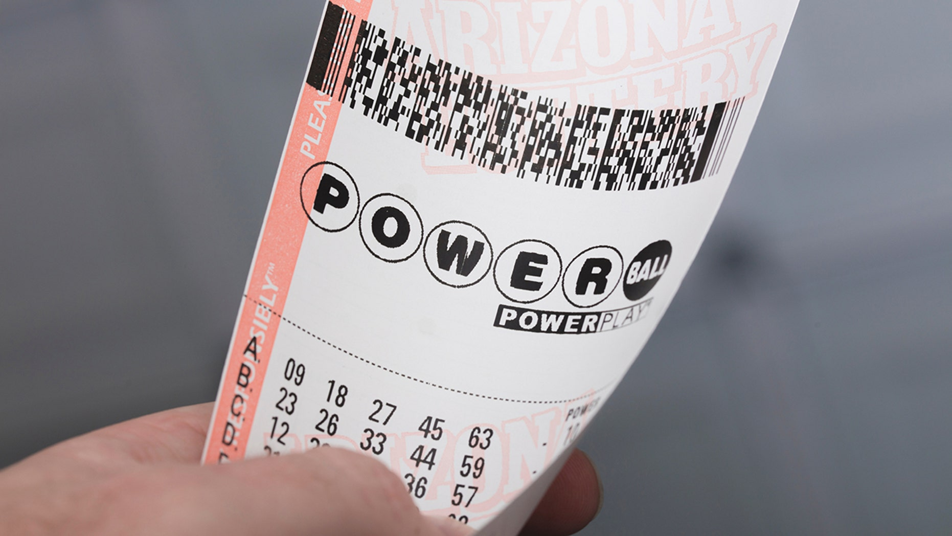 A man holds a Powerball lottery ticket in Kingman, Ariz.